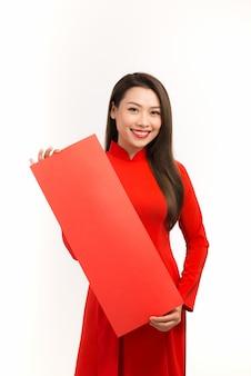 Aziatische vrouw in ao dai traditionele rode jurk met lege rode labelkopieerruimte in het nieuwe maanjaar