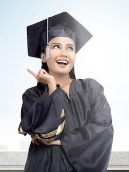 Aziatische vrouw in barethoed die van universiteit een diploma behalen