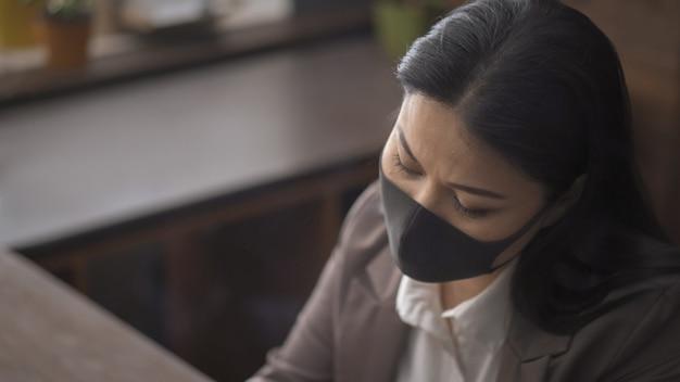 Aziatische vrouw in beschermend masker dat laptop met behulp van