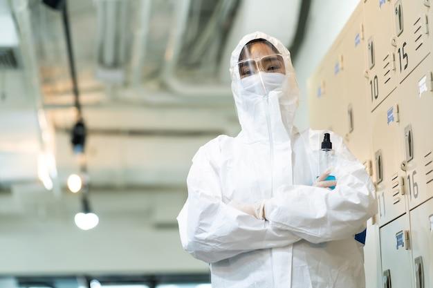 Aziatische vrouw in beschermend pak en masker dat in bureau desinfecteert. bescherming tegen de ziekte van covid-19