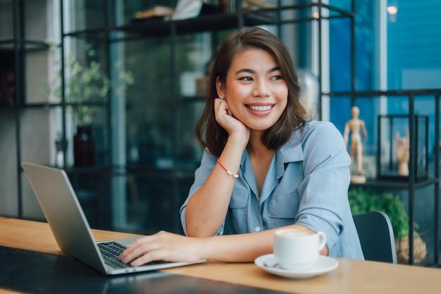 Aziatische vrouw in blauw shirt in café koffie drinken en praten met de glimlach van de jongensvriend en een blij gezicht