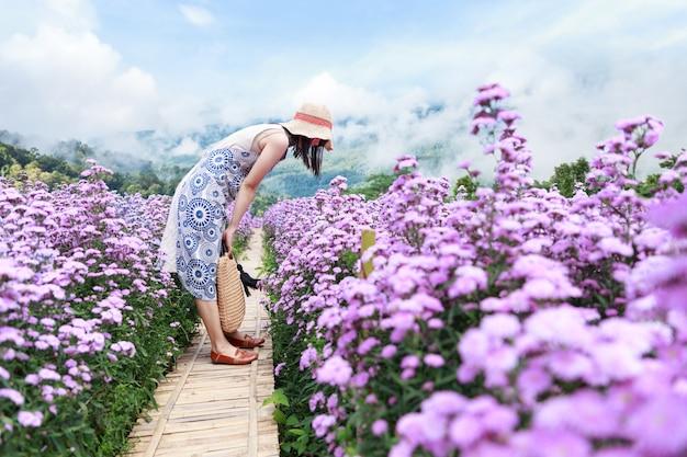 Aziatische vrouw in bloementuin.