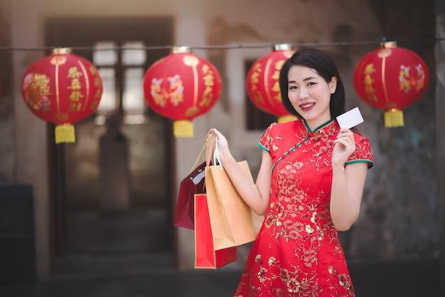 Aziatische vrouw in cheongsam rode jurk bedrijf boodschappentas en krediet in chinees nieuwjaar