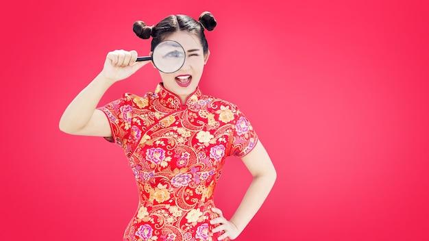 Aziatische vrouw in chinese cheongsamjurk gebruikt manifier om actie op rood concept te zoeken