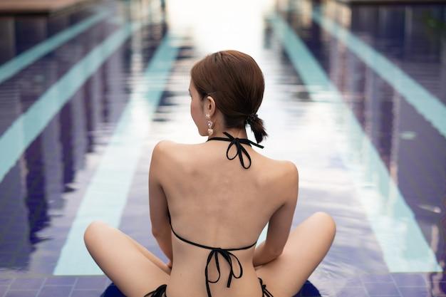 Aziatische vrouw in de zwarte bikini poseren in de buurt van het zwembad.