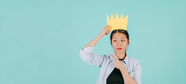 Aziatische vrouw in document kroon die links richt