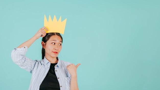 Aziatische vrouw in document kroon die net richt