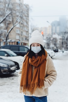 Aziatische vrouw in een beschermend masker dat langs een sneeuwstraat loopt. coronavirus concept