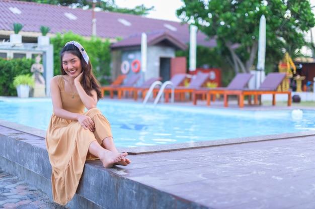 Aziatische vrouw in een bruine jurk relax voel me gelukkig. met toerisme bij het zwembad