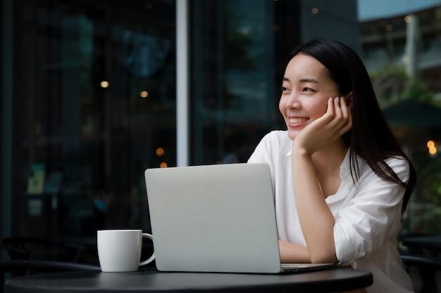 Aziatische vrouw in een café die op een laptop werkt