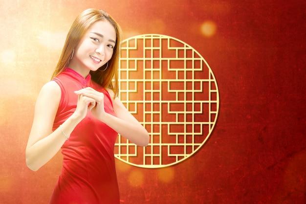 Aziatische vrouw in een cheongsam jurk met gefeliciteerd gebaar