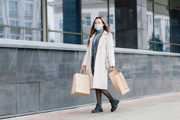 Aziatische vrouw in een jas, bril en een medisch masker staat op straat en houdt een pakket in haar handen.