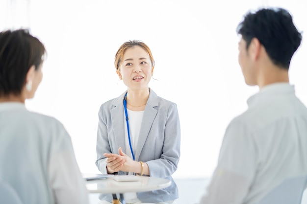 Aziatische vrouw in een pak die uitleg geeft aan een stel
