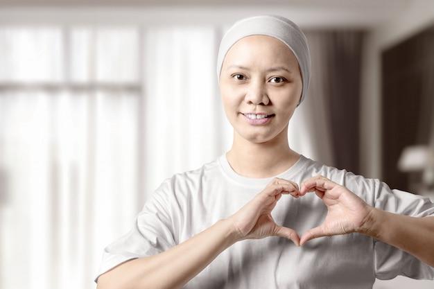 Aziatische vrouw in een wit overhemd die een hartteken met haar handen op het huis tonen