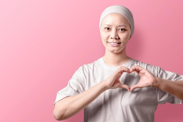 Aziatische vrouw in een wit overhemd die een hartteken met haar handen op roze tonen