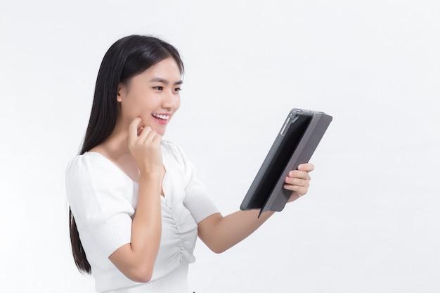 Aziatische vrouw in een wit overhemd kijkt vrolijk naar de tablet met een witte achtergrond.