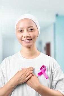 Aziatische vrouw in een wit shirt met een roze lint in het ziekenhuis