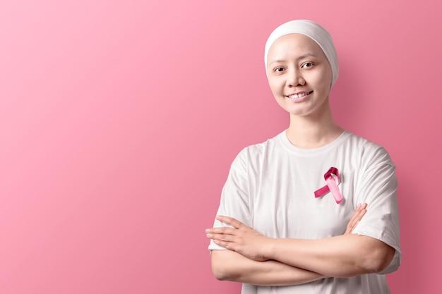 Aziatische vrouw in een wit shirt met roze lint op roze
