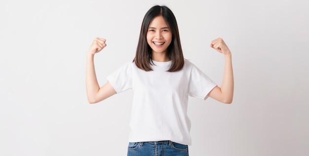 Aziatische vrouw in een wit t-shirt heft armen en gebalde vuisten