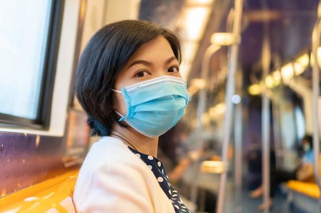Aziatische vrouw in gezichtsmasker voor coronavirusbescherming in forenzentrein die naar werk reizen