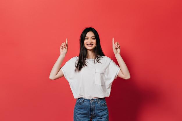 Aziatische vrouw in goed humeur toont haar vingers om tekst op de rode muur te plaatsen