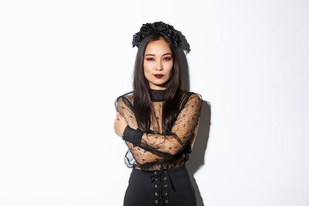 Aziatische vrouw in halloween-kostuum het stellen