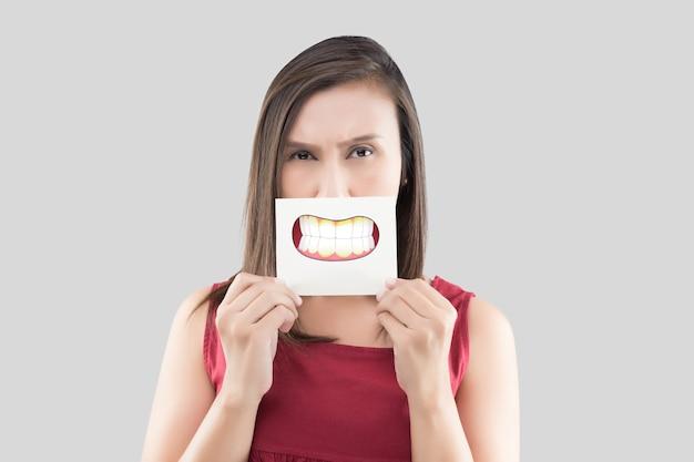 Aziatische vrouw in het rode shirt met een bruin papier met de tandplak cartoon afbeelding van zijn mond tegen de grijze muur, slechte adem of halitose, het concept met tandvlees en tanden van de gezondheidszorg