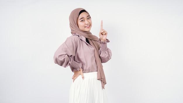 Aziatische vrouw in hijab wijzend naar de lege ruimte boven geïsoleerd op een witte achtergrond