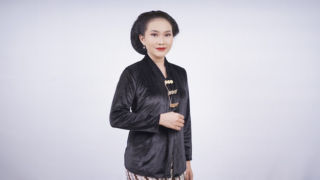 Aziatische vrouw in kebaya die schuin staat ziet er mooi uit geïsoleerd op een witte achtergrond
