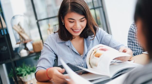 Aziatische vrouw in koffie die met groepswerk en klantenglimlach en gelukkig gezicht werkt