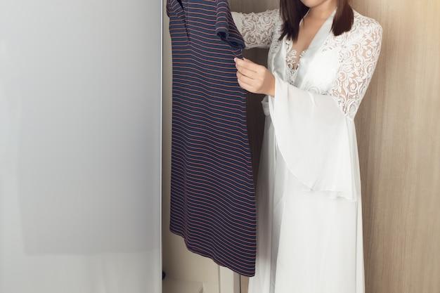 Aziatische vrouw in lange witte nachtjapon die kleren in garderobe kiezen