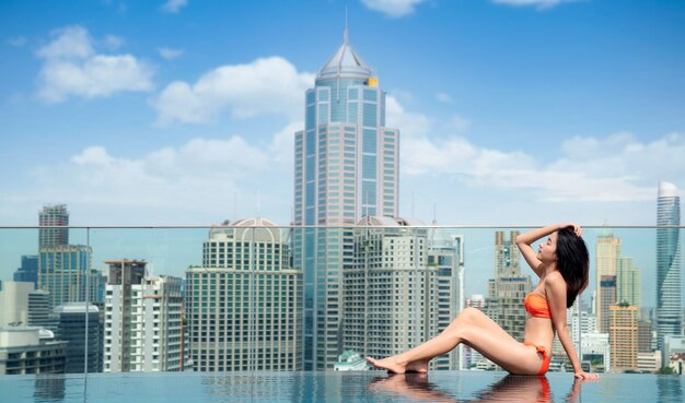 Aziatische vrouw in oranje zwembroek ontspannen in zwembad op het dak met de stad bangkok