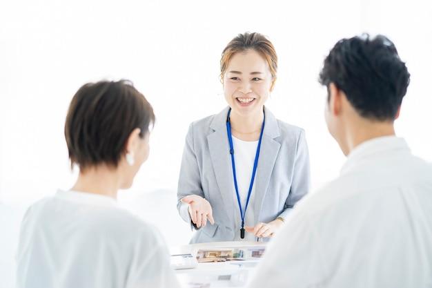 Aziatische vrouw in pak die onroerend goed verkoopt aan een stel