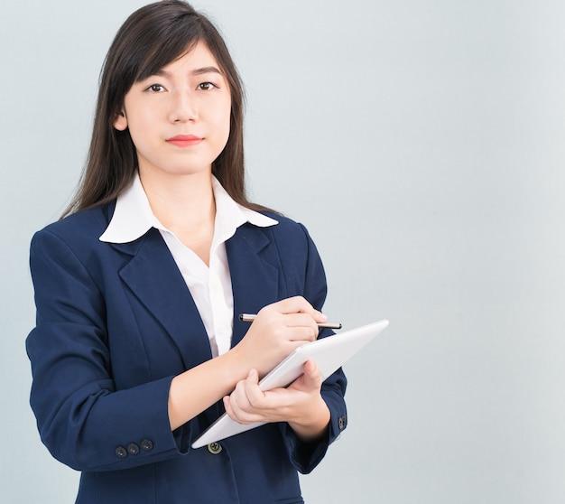 Aziatische vrouw in pak met behulp van computer digitale tablet geïsoleerd op een grijze achtergrond