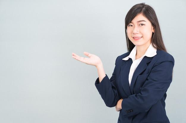 Aziatische vrouw in pak open hand palm gebaren met lege ruimte geïsoleerd op een grijze achtergrond
