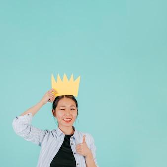 Aziatische vrouw in papier kroon gebaren duim-omhoog