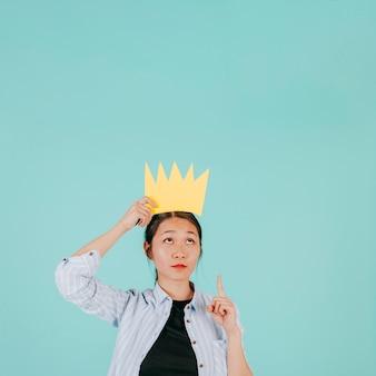 Aziatische vrouw in papieren kroon die omhoog wijst