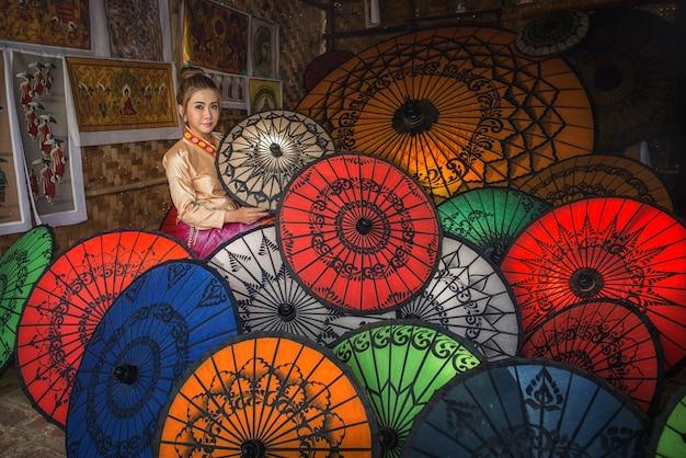 Aziatische vrouw in paraplu souvenier shop in new bagan in myanmar in southeastasia