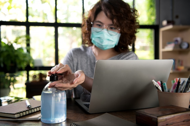 Aziatische vrouw in quarantaine en sociaal afstandelijk dragend chirurgisch masker en het schoonmaken van handen met alcoholgel ontsmettingsmiddel terwijl het werken van huis tijdens covid-19 coronavirus pandemie