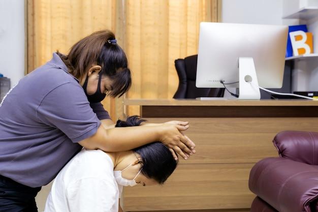 Aziatische vrouw in quarantaine masseren thuis met gezichtsmasker