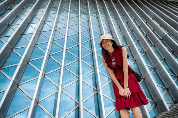 Aziatische vrouw in rode jurk bij modern gebouw, vrouwelijk meisje met stedelijke stadslevensstijl