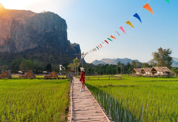 Aziatische vrouw in rode jurk met hoed staande op houten brug over groene rijstveld kijken naar grote bergzicht (phu pha man) in khonkaen, thailand, landschap van verse rijst boerderij en heuvel