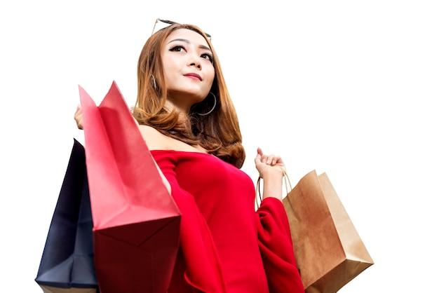 Aziatische vrouw in rode kleding en zonnebril die het winkelen zakken dragen