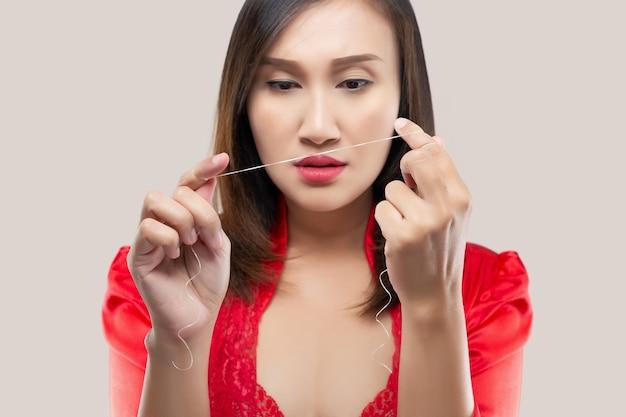 Aziatische vrouw in rode zijden gewaad schoonmakende tanden met tandzijde op roze