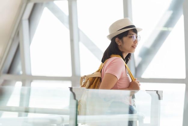 Aziatische vrouw in roze shirt bril, hoed met gele rugzak wacht op de vlucht in de hal van de luchthaven.