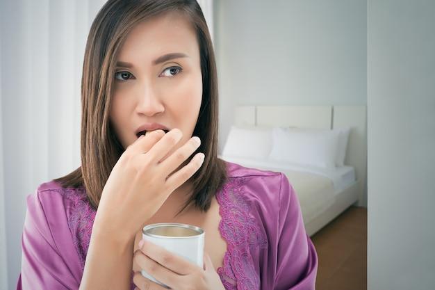 Aziatische vrouw in satijn purpere nachthemden die ingeblikte bonen eten bij slaapkamer
