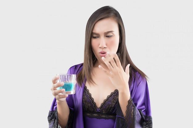 Aziatische vrouw in sexy zijden nachtpon en paarse gewaad voelen branden in haar mond