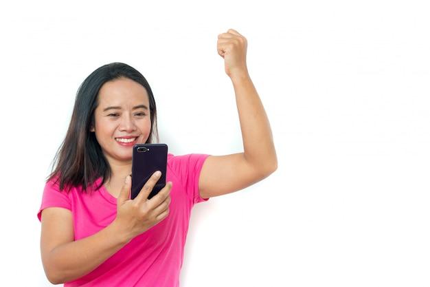 Aziatische vrouw in t-shirt met smartphone over witte achtergrond.