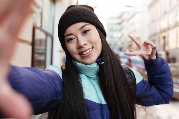 Aziatische vrouw in warme kleren maken selfie