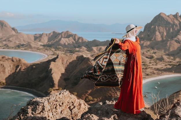Aziatische vrouw in zomerhoed en jurk die op de top van de heuvel staat en kain songket vasthoudt op padar island l